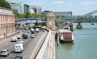 Le 9 juillet 2018, à Paris. Des voitures circulent sur une route à cinq voies, quai de la Rapée (à gauche). Le métro de la ligne 5 passe sur le vidauc d'Austerliz, qui enjambe la Seine.