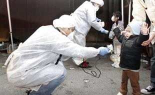 Des experts sanitaires examinent des enfants pour vérifier s'ils montrent des signes de radiation, près de la centrale de Fukushima Daini, à Koriyama, le 13 mars 2011.