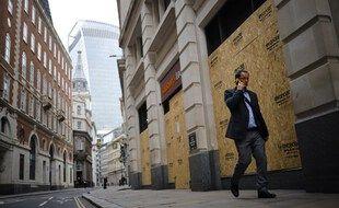 Un homme marche dans une rue désertée de la City, le quartier d'affaires londonnien.