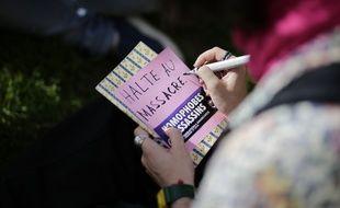 Une manifestante écrit «Halte au massacre» durant une manifestation contre les violences homophobes en Tchétchénie, le 23 mai 2017 devant l'ambassade du Russie à Paris.