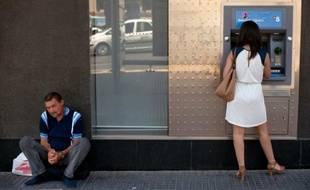 Un homme mendie pendant une femme retire de l'argent à Malaga le 27 juin 2014
