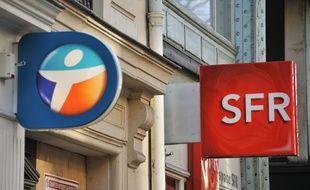 Les logos de Bouygues Telecom et SFR devant un magasin parisien.