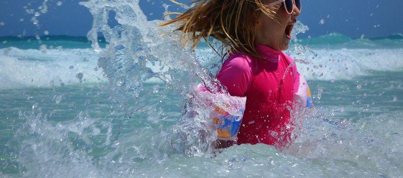 Les dermatologues conseillent d'équiper les plus jeunes d'un vêtements anti-UV pour se baigner.
