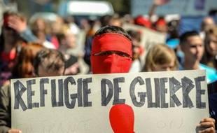 """Un homme masqué tient une pancarte où est inscrit """"Réfugié de guerre"""" lors d'une marche en mémoire des migrants morts en tentant de rejoindre l'Angleterre, le 8 août 2015 à Calais"""