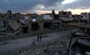 Des enfants dans les ruines d'une rue de Douma, en périphérie de la capitale syrienne Damas, le 27 février 2016