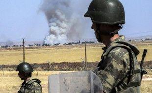 Des soldats turcs observent, par-dessus la frontière avec la Syrie, la fumée des combats dans Kobané, le 25 juin 2015 près de Suruc, en Turquie