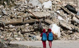 Deux petites Syriennes portant des cartables fournis par l'Unicef dans les rues dévastées d'Alep (Syrie), en mars 2015. AFP PHOTO / AMC / ZEIN AL-RIFAI