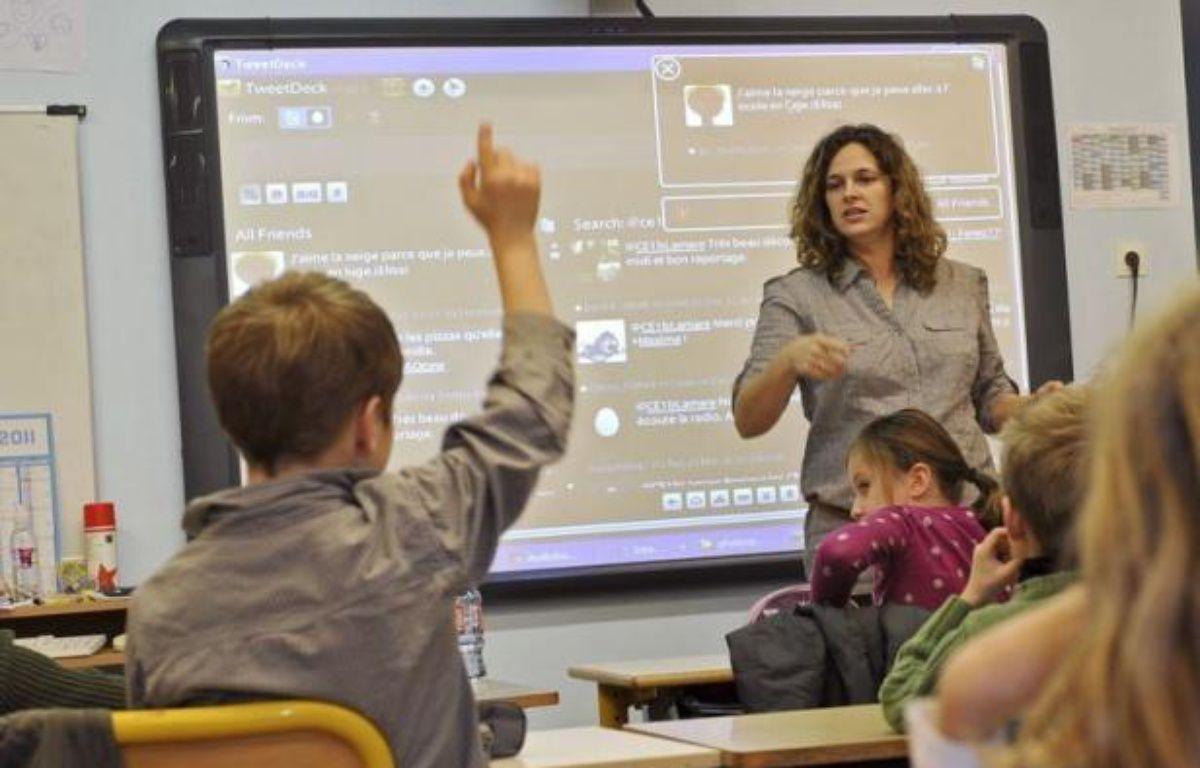"""Une forêt de doigts levés pour la lecture à haute voix et pour les exercices d'écriture... Seul Twitter suscite de telles réactions chez les enfants d'une école de Seclin, dans le nord de la France, l'une des premières du pays à utiliser le site de micro-blogging. """"Sur Twitter, il y a l'image, le son, mais ça ne leur enlève pas l'intérêt pour l'écriture, au contraire"""", sourit Céline Lamare, institutrice d'une classe pour des enfants de 7 ans de l'école privée de l'Immaculée Conception. – Philippe Huguen afp.com"""