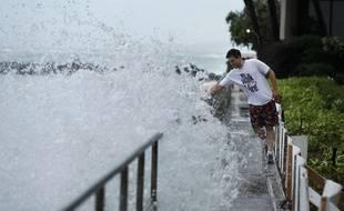 Un homme tente d'éviter une vague le long d'une plage d'Honolulu, alors que l'ouragan Lane approche doucement l'île d'Hawaii, le 24 août 2018.