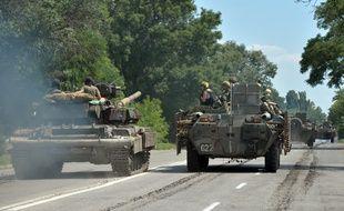 Une colonne de chars de l'armée ukrainienne traverse la ville de Druzhkivka, au nord de Donetsk. L'armée russe amasserait aussi ses forces dans cette zone à la frontière russo-ukrainienne.