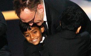Le réalisateur britannique Danny Boyle enlace les acteurs Azharuddin Ismael (G) et Ayush Mahesh (D) après avoir remporté l'Oscar du meilleur film pour «Slumdog Millionaire», Hollywood, le 22 février 2009.  >> Retrouvez la cérémonie en images ici >>