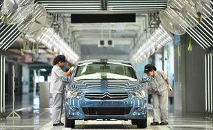 Des employés d'une usine de Dongfeng PSA Peugeot Citroën travaillent dans une usine de Wuhan, en Chine, le 2 juillet 2013