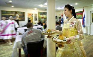 En robe cloche de soie jaune brodée, miss So accueille avec un sourire timide les clients du Pyongyang, le premier restaurant nord-coréen en Europe, selon ses propriétaires, qui vient d'ouvrir à Amsterdam.