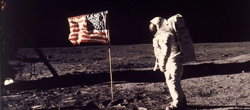 """Sur cette photo prise par l'astronaute Neil Armstrong, son collègue Edwin E. """"Buzz"""" Aldrin Jr. pose à côté du drapeau américain déployé sur la lune lors de la mission Apollo 11."""