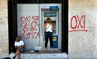 """Une femme retire de l'argent à un distributeur bancaire non loin d'un mendiant et de graffitis disant """"non à la peur"""", à Thessalonique, le 6 juillet 2015"""