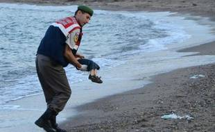 Un policier turc transporte le corps d'un enfant échoué sur une plage de Bodrum en Turquie, après le naufrage d'un bateau transportant des migrants, le 2 septembre 2015