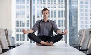 Illustration d'un homme méditant dans une salle de réunion.