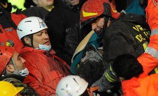 Les sauveteurs extraient un homme blessé de sa maison, à Aquila.