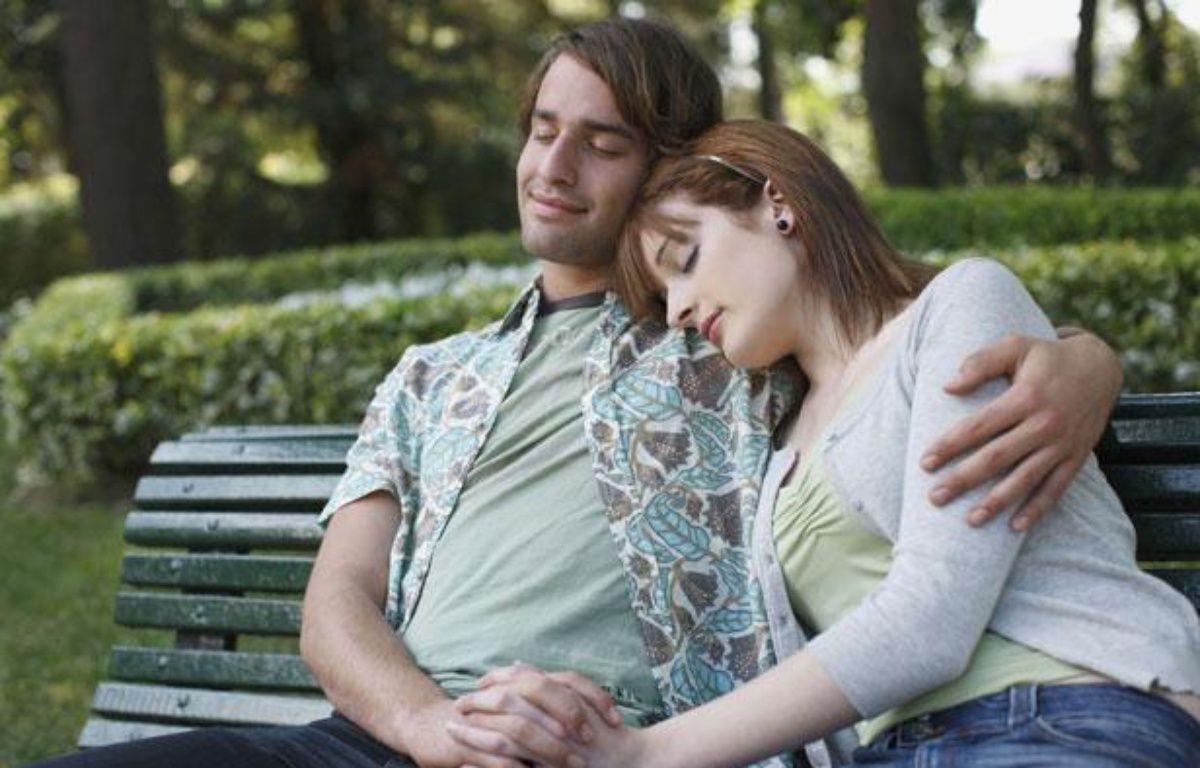 Illustration: Un couple fait la sieste sur un banc dans un parc. – SIPA
