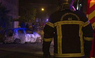Un policier intervient sur des incendies de voitures à Nantes dans la nuit du jeudi 5 juillet au vendredi 6 juillet 2018.