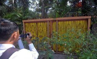 Un journaliste filme l'ancien portail métallique de la résidence de l'opposante birmane Aung San Suu Kyi, le 31 janvier 2015 à Rangoun
