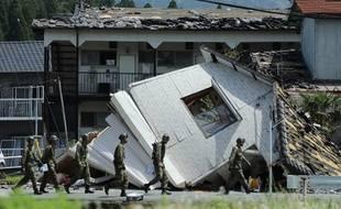 Illustration: Des soldats passent devant une maison effondrée à Minami-Aso, dans la préfecture de Kumamoto, le 22 avril 2016, après qu'un séisme a frappé la région.
