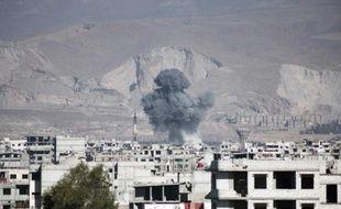 De la fumée s'élève d'un immeuble après un raid aérien des forces gouvernementales dans la ville d'Arbin en Syrie, le 17 février 2016
