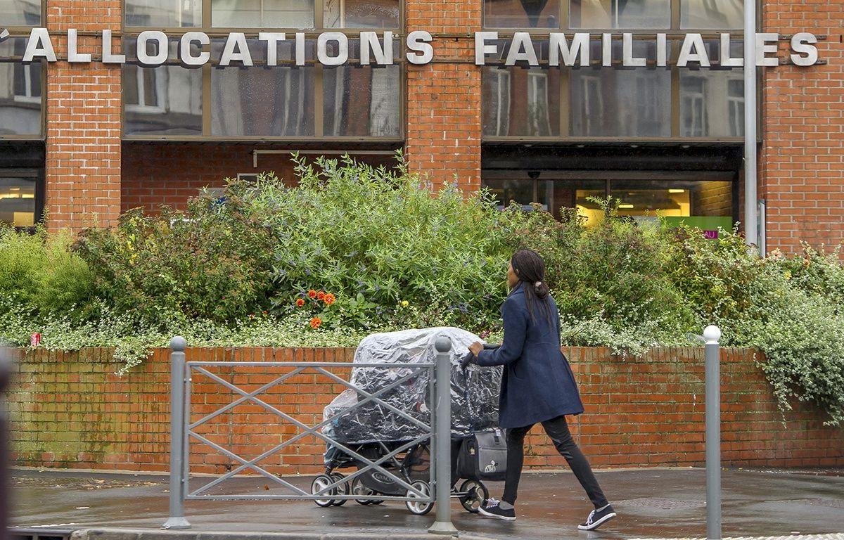 Une femme poussant un landau passe devant la Caisse d'allocations familiales à Lille le 8 octobre 2014  – Philippe Huguen AFP