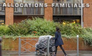 Une femme poussant un landau passe devant la Caisse d'allocations familiales à Lille le 8 octobre 2014