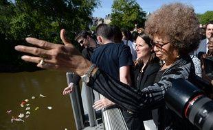 Angela Davis, ici a côté de Johanna Rolland, lance des fleurs dans la Loire dimanche après-midi. AFP  / JEAN-SEBASTIEN EVRARD