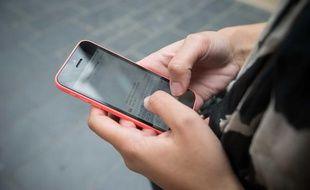 Illustration d'une jeune femme envoyant un sms avec un iphone 5c, le 8 octobre 2013 à Bordeaux