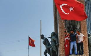Des opposants au putsch agitent un drapeau turc sur la place Taksim à Istanbul.