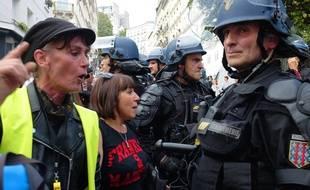 Des manifestantes dont l'une portant un gilet jaune face à des forces de l'ordre, le 31 août 2019 à Paris