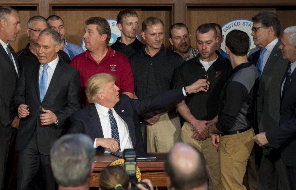 Donald Trump entouré de mineurs de Pennsylvanie, le 28 mars 2017, lors de la signature du décret remettant en cause le Clean Power Plan. – JIM WATSON / AFP