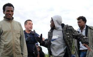 Un policier tente de stopper des migrants le 3 août 2015 à Coquelles près de Calais