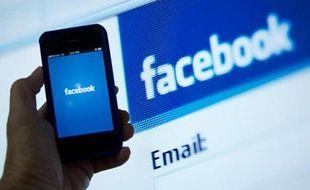 Un smartphone devant une page d'accueil de Facebook