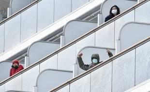 Un passager à bord du bateau de croisière Diamond Princess salue les médias à son arrivée au port de Yokohama le 6 février 2020.