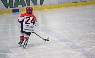 Un enfant jouant au hockey sur glace. Illustration.
