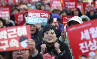 Un manifestant porte un masque à l'image de Park Geun-hye, lors d'une manifestation réclamant son arrestation le 27 mars 2017.