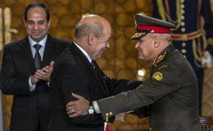 Le ministre français de la Défense Jean-Yves Le Drian (c) serre la main du général egyptien Sedki Sobhi (d), sous les yeux du président, Abdel Fattah al-Sissi, au Caire, le 16 février 2015