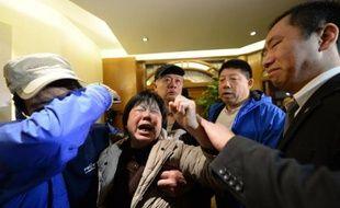 Des proches des passagers du vol MH370 pleurent à l'annonce des autorités malaisiennes, à Pékin le 24 mars 2014
