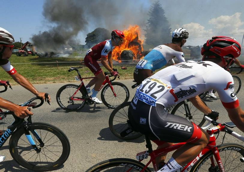 The pack rides past a burning haystack during the sixth stage of the Tour de France cycling race over 181 kilometers (112.5 miles) with start in Brest and finish in Mur-de-Bretagne Guerledan, France, Thursday, July 12, 2018.