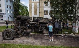 Un Ukrainien examine un véhicule utilisé par les rebelles prorusses et qui a été détruit le 27 mai 2014 par l'armée ukrainienne dans la ville de Donetsk, dans l'est du pays