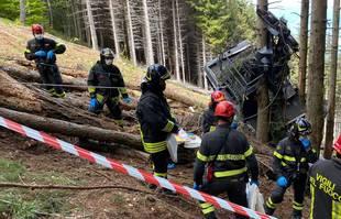Des sauveteurs travaillent près de l'épave d'un téléphérique après sa chute dans la région du Piémont, dans le nord de l'Italie, le 23 mai 2021.