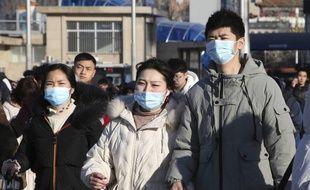 Des Chinois se protègent contre une étrange maladie.