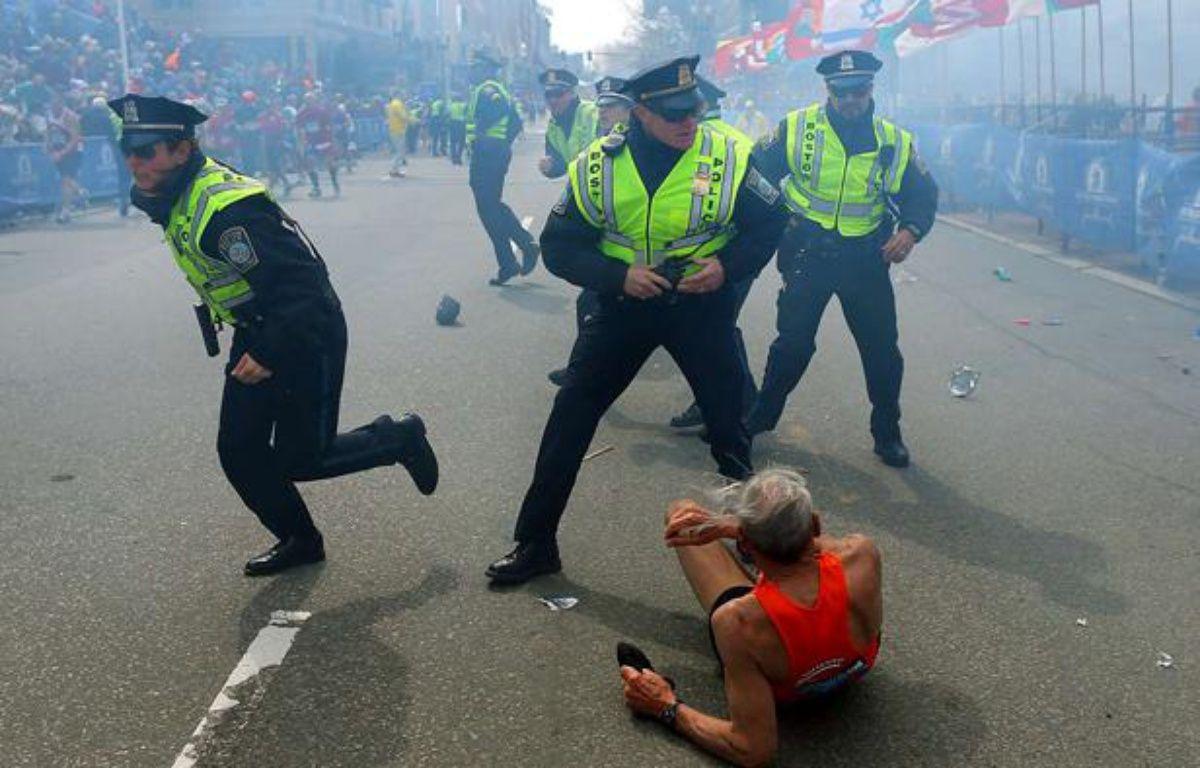Un coureur est allongé sur le sol, alors que des policiers réagissent après la seconde explosion survenue lors du marathon de Boston – John Tlumacki/AP/SIPA