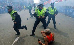 Un coureur est allongé sur le sol, alors que des policiers réagissent après la seconde explosion survenue lors du marathon de Boston