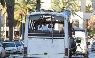 Des enquêteurs de la police scientifique relèvent des indices sur la carcasse d'un bus de la sécurité présidentielle cible d'un attentat à la bombe en plein centre de Tunis, le 25 novembre 2015