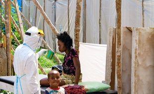 Un travailleur de santé en combinaison de protection soigne une mère et son fils en Sierra Leone, en juillet 2014.