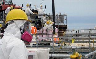 Photo publiée par Tepco le 18 juillet 2013 et montrant des ouvriers à l'oeuvre dans la centrale accidentée de Fukushima